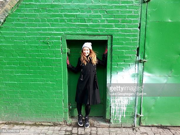 Full Length Of Happy Young Woman Standing In Doorway Of Green House