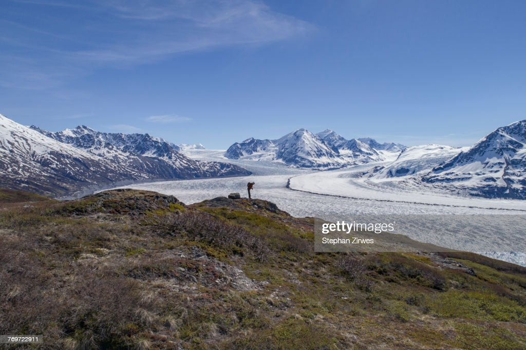 Full length of hiker looking at glacier against blue sky, Knik Glacier, Palmer, Alaska : Stock Photo