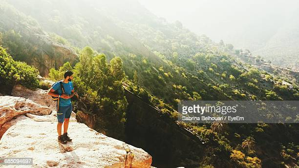 Full Length Of Hiker On Cliff Looking At Mountain