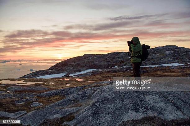 Full Length Of Hiker Photographing While Standing On Rock Against Sky During Sunset