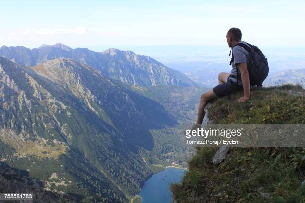 Full Length Of Hiker Sitting On Cliff While Looking At Tatra Mountains