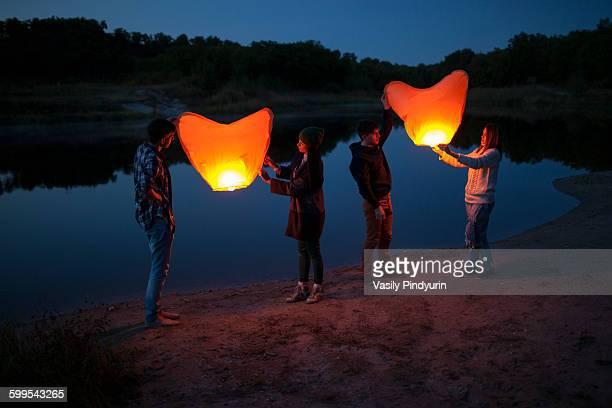 Full length of hikers releasing paper lanterns at lakeshore