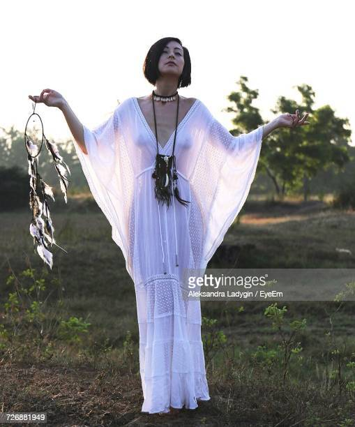 Full Length Of Hippie Woman Holding Dreamcatcher While Standing On Field