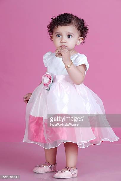 Full length of innocent girl eating cookie against pink background