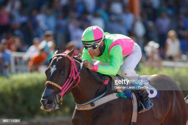 full length of jockey riding horse - horse racing stock pictures, royalty-free photos & images