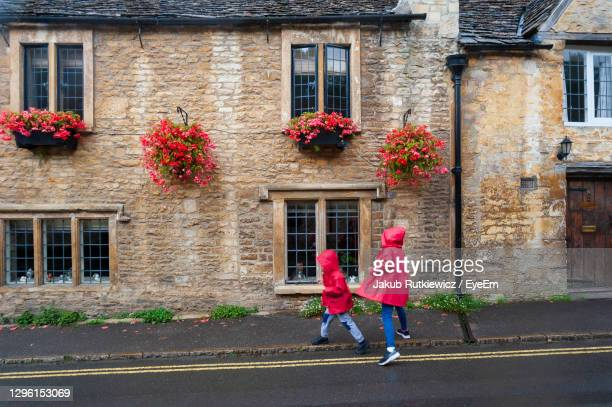 full length of kids playing on road against houses - town stock pictures, royalty-free photos & images