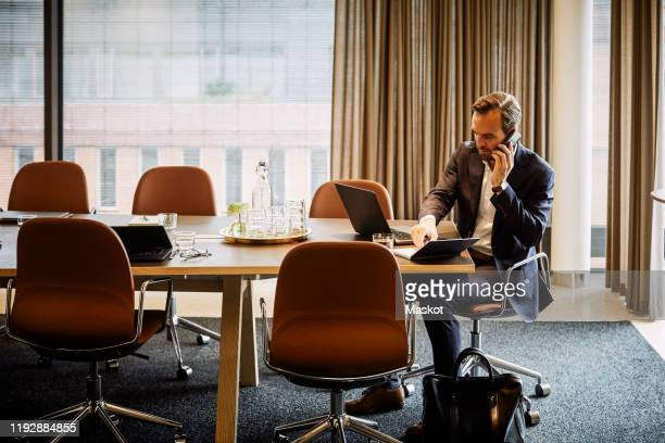 full length of legal professional talking on mobile phone while writing in diary at board room - 法律関係の職業 ストックフォトと画像