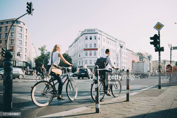 full length of male and female entrepreneurs riding bicycle on road in city - verkehrswesen stock-fotos und bilder