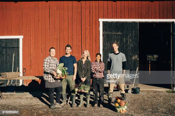 Full length of male and female farmers with organic vegetables standing outside barn