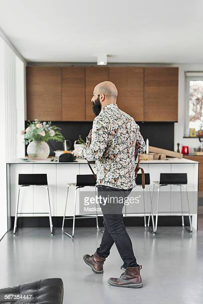 Full length of male art director walking in kitchen