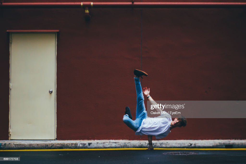 Full Length Of Male Dancer Breakdancing On Street By Maroon Wall : Stock Photo