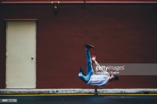 Full Length Of Male Dancer Breakdancing On Street By Maroon Wall