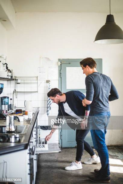 full length of male programmers standing in kitchen at creative office - 引き出し ストックフォトと画像