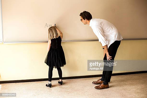 full length of male teacher watching girl writing on whiteboard - bending stock pictures, royalty-free photos & images