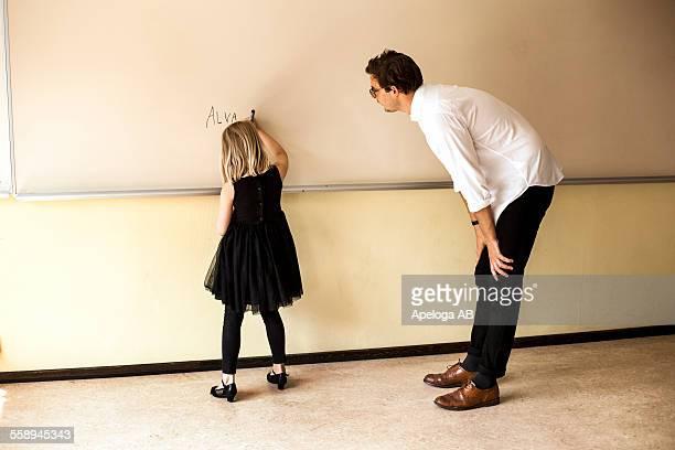 full length of male teacher watching girl writing on whiteboard - beugen oder biegen stock-fotos und bilder