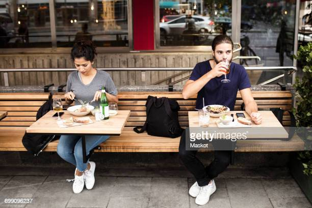 full length of man and woman having lunch at sidewalk cafe - woman sitting on man's lap stock pictures, royalty-free photos & images
