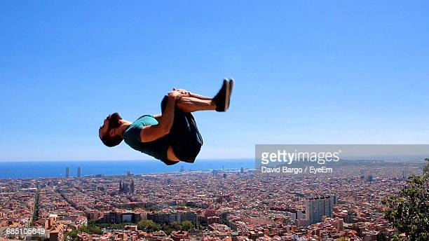Full Length Of Man Backflipping Over Buildings Against Clear Blue Sky On Sunny Day