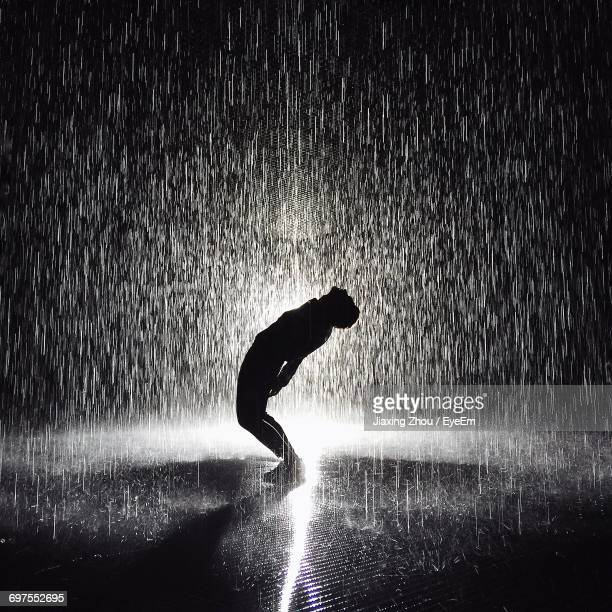 full length of man bending over backwards while standing on street during rainy season - heavy rain stockfoto's en -beelden