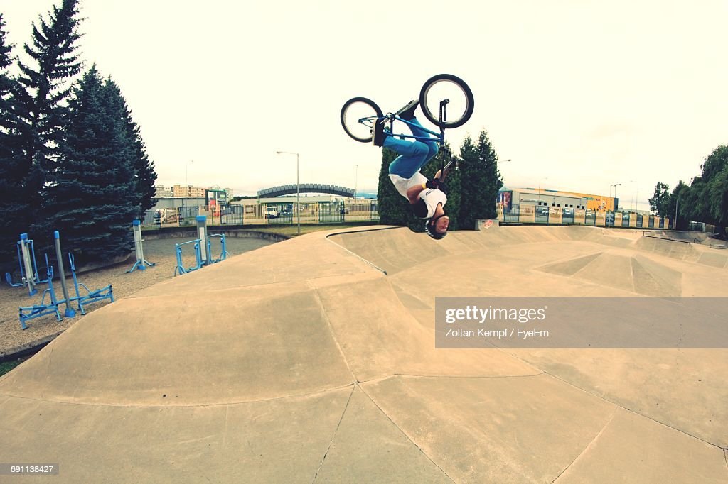 Full Length Of Man Bmx Cycling Over Sports Ramp : Stock Photo