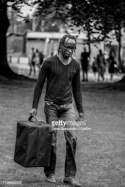 full length of man carrying luggage on field - steve guessoum stockfoto's en -beelden