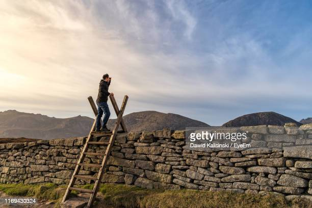 full length of man climbing on ladder against sky - retaining wall stock pictures, royalty-free photos & images