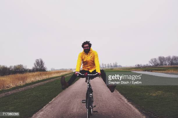 Full Length Of Man Cycling On Field Against Sky