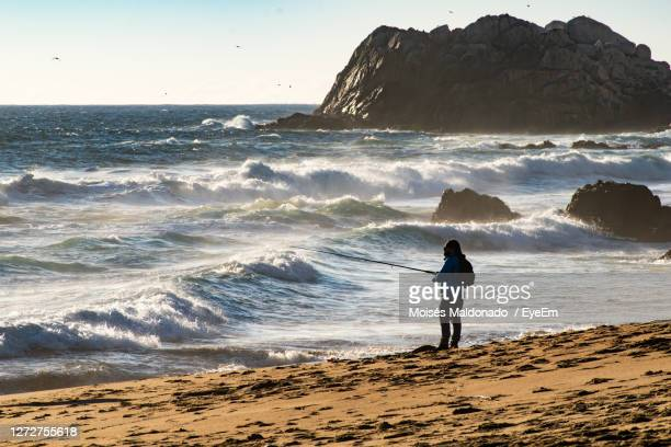 full length of man fishing on beach against sky - vina del mar stock pictures, royalty-free photos & images