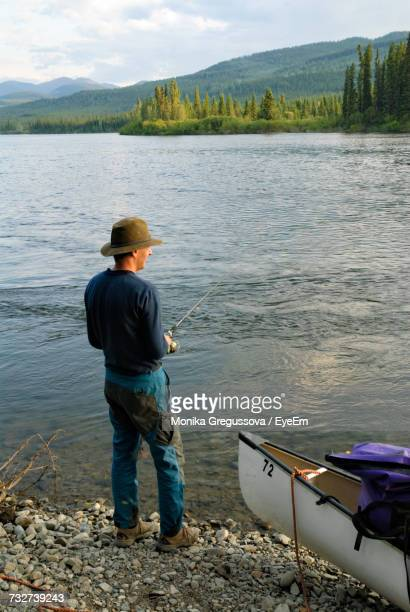 full length of man fishing while standing by yukon river - monika gregussova stock pictures, royalty-free photos & images