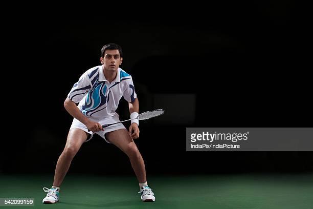 Full length of man holding badminton racket at court