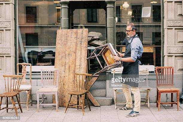Full length of man holding chair while arranging outside store