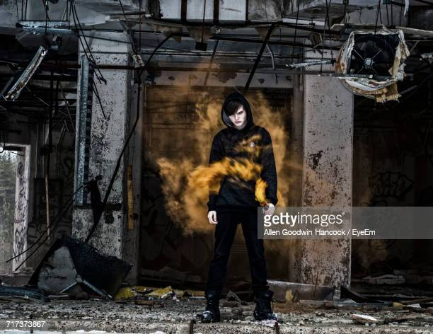 Full Length Of Man Holding Distress Flare In Abandoned Building
