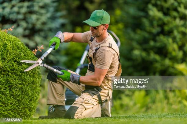 full length of man holding golf course - landscaped stock pictures, royalty-free photos & images