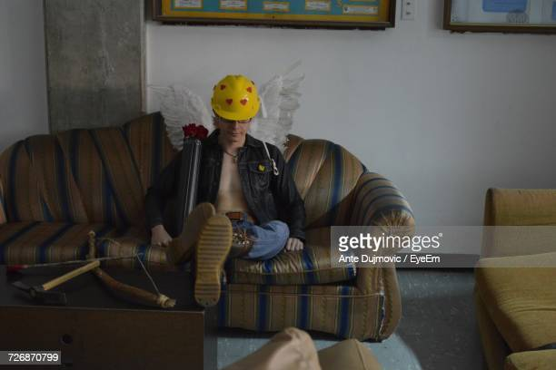 Full Length Of Man In Costume Sitting On Sofa At Home