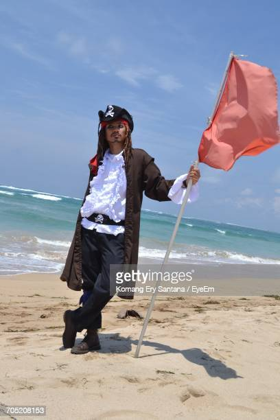 Full Length Of Man In Pirate Costume Holding Flag At Beach Against Sky