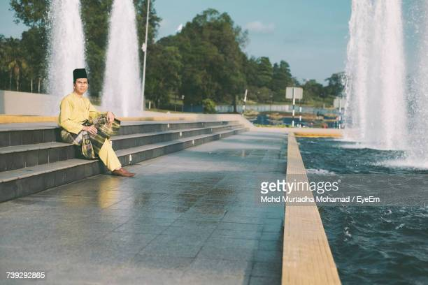 Full Length Of Man In Traditional Clothing Sitting On Steps By Fountain