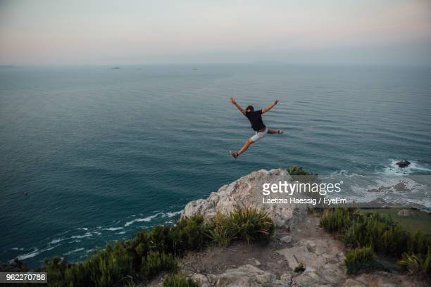 Full Length Of Man Jumping Against Sea And Sky During Sunset