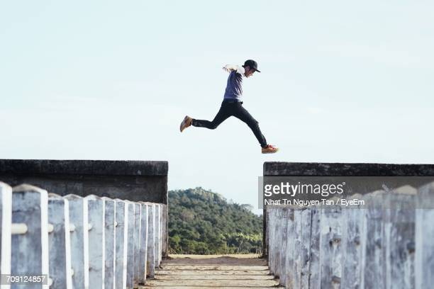 full length of man jumping against sky - 境界 ストックフォトと画像