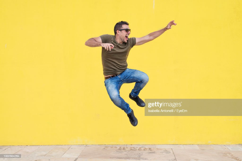 Full Length Of Man Jumping Against Yellow Wall : Stock Photo