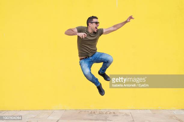 full length of man jumping against yellow wall - eccitazione foto e immagini stock