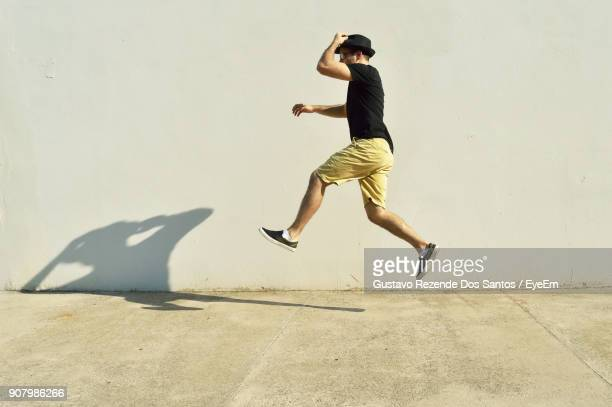 Full Length Of Man Jumping By Wall