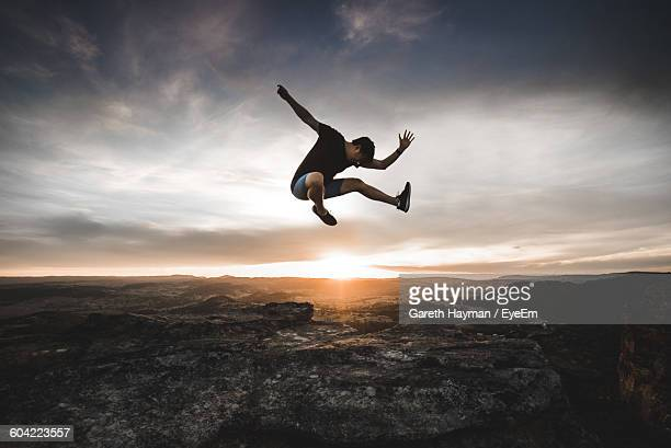 full length of man jumping over mountain against cloudy sky at sunset - jumping stock pictures, royalty-free photos & images