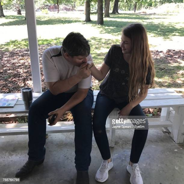 Full Length Of Man Kissing Girlfriend While Sitting On Bench At Park