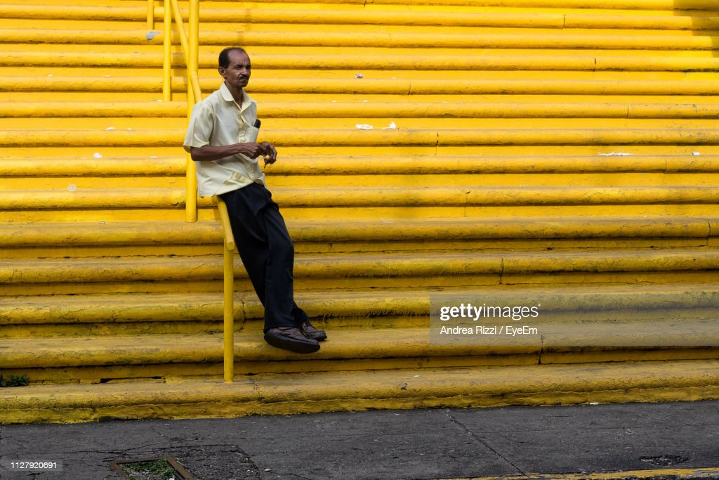 Full Length Of Man Leaning On Railing At Yellow Steps : Foto stock