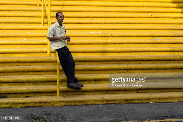 Full Length Of Man Leaning On Railing At Yellow Steps