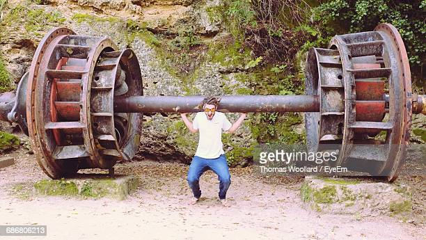 Full Length Of Man Lifting Huge Old Machinery Part