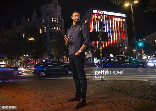 Full length of man looking away holding smart phone in city at night