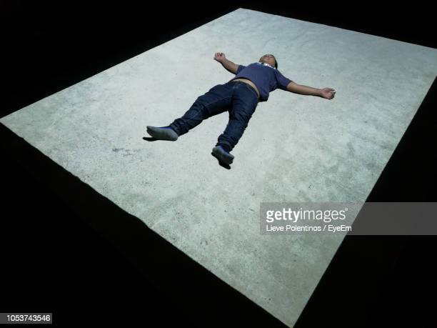 full length of man lying down on floor - lying down stock pictures, royalty-free photos & images