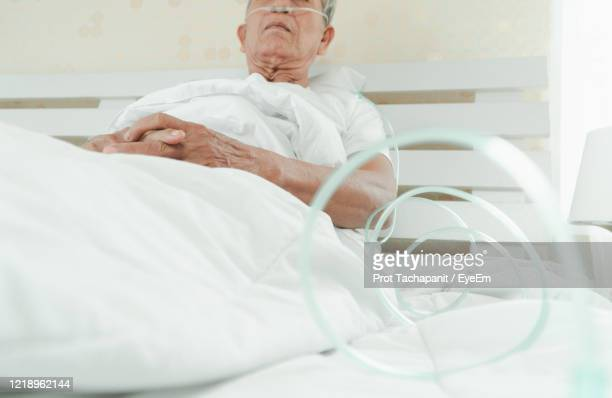 full length of man lying on bed - sepsis stock pictures, royalty-free photos & images