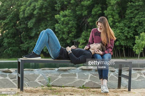 full length of man lying on girlfriends lap at park - woman sitting on man's lap stock pictures, royalty-free photos & images