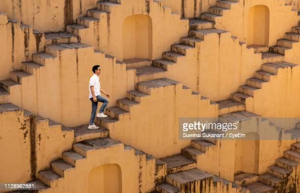 full length of man moving up on steps - moving up stock pictures, royalty-free photos & images